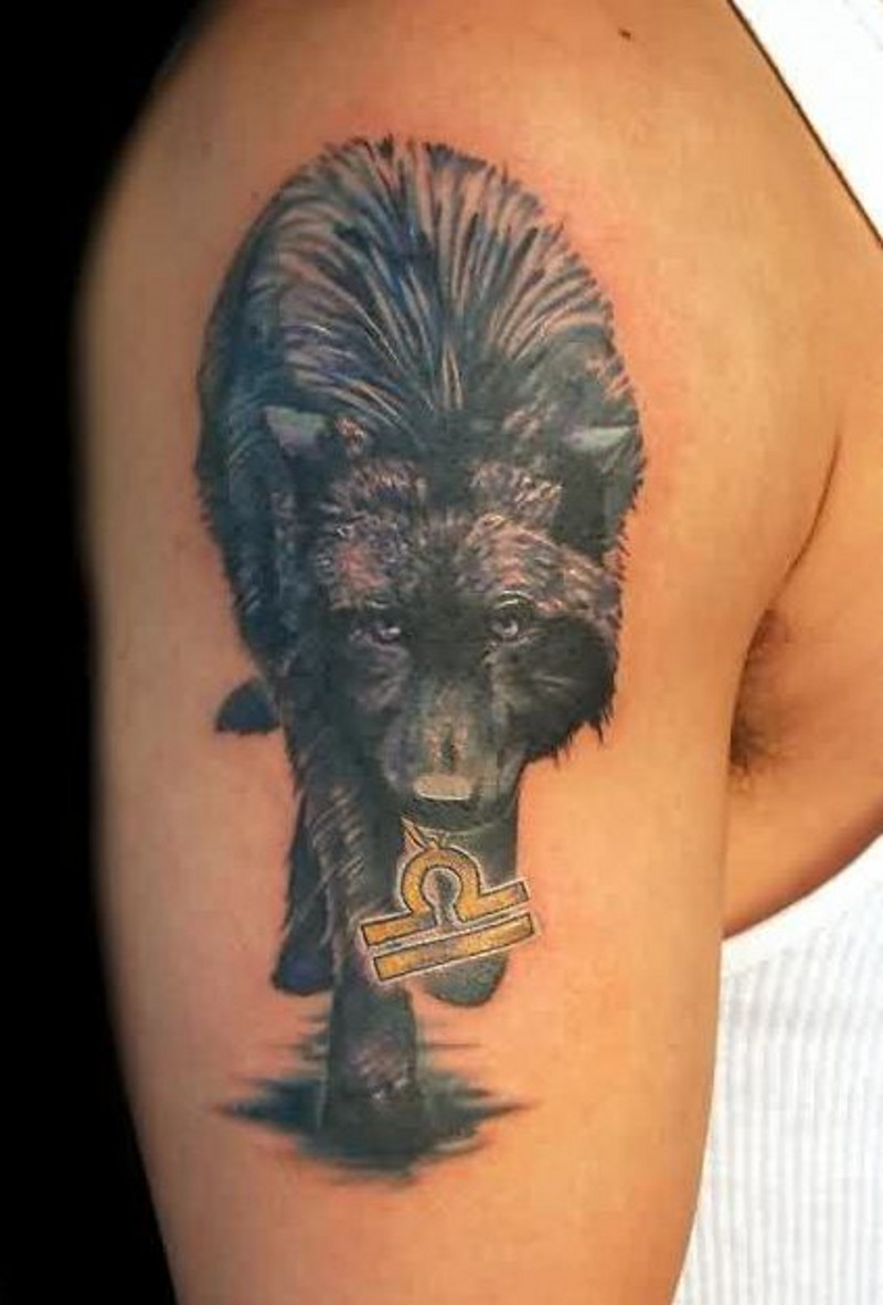 Dark a wolf with a sign in mouth tattoo on shoulder