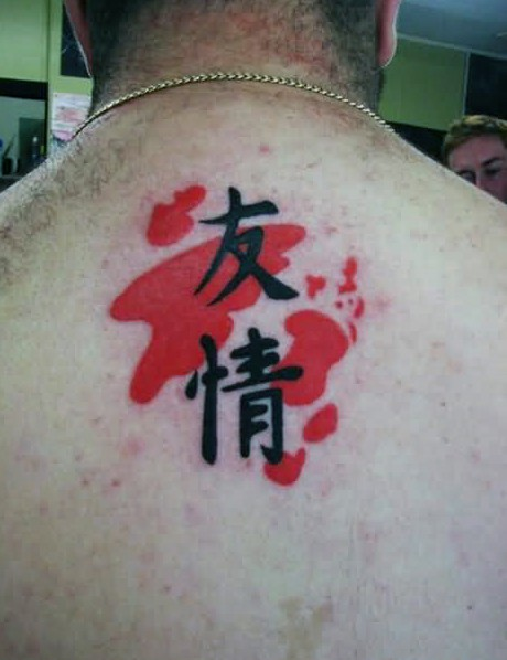 Dark black Asian hieroglyphs with red ink elements tattoo on man&quots upper back