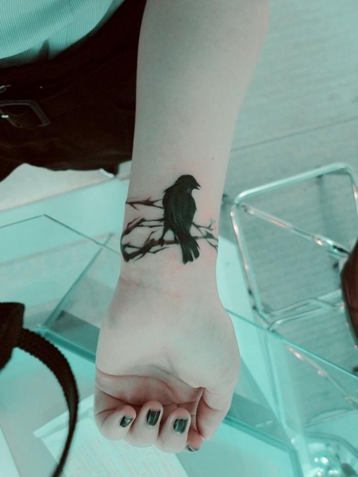 Dark black crow sitting on branch mystical lady&quots wrist tattoo