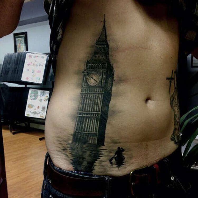 Dark black ink belly tattoo of Big Ben in sea