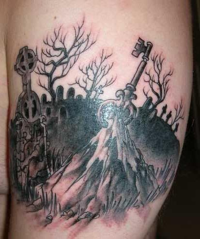 Dark black ink cemetery tattoo on shoulder with mystic key