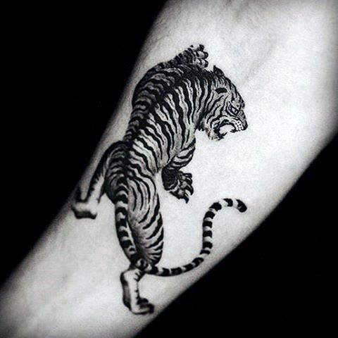 Dark black ink forearm tattoo of tiger