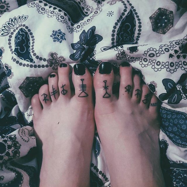 Dark black ink small size runes tattoo on toes
