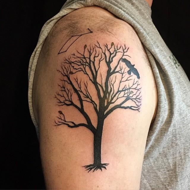 Dark black ink tree with several leaves and roots shoulder tattoo with black crow