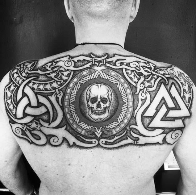 Dark black ink upper back tattoo of human skull with various symbols