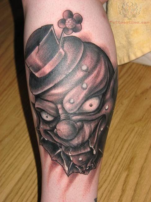 pagliaccio scuro in capello con fiore tatuaggio sulla gamba
