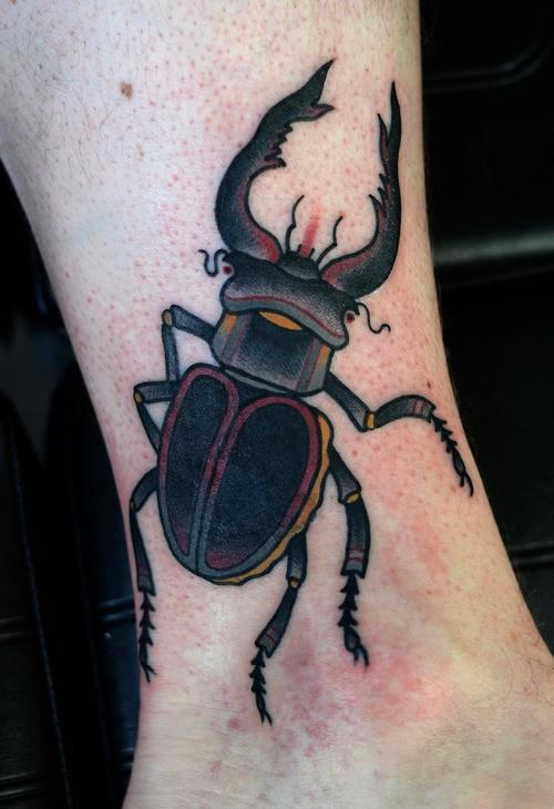 Dark color bug tattoo on ankle