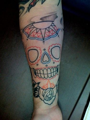 Semplice teschio colorato tatuato sul braccio