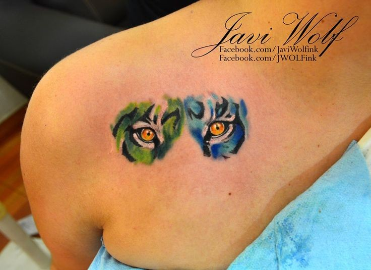 Deep look of tiger&quots eyes green and blue side colored tattoo on shoulder blade by Javi Wolf