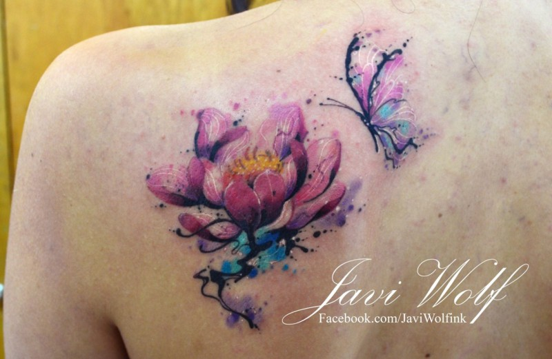 Delicate pink lotus flower and flying butterfly colored tattoo on shoulder blade by Javi Wolf in watercolor style