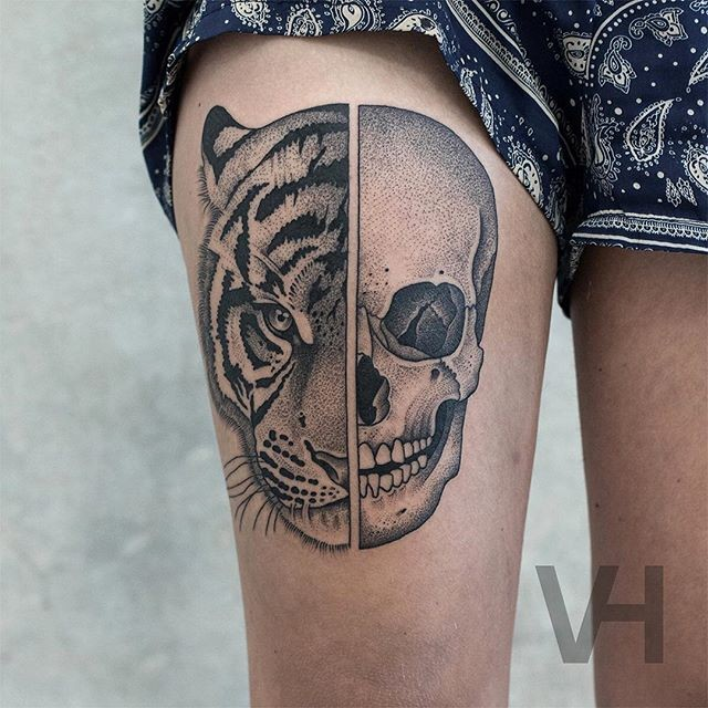 Designed by Valentin Hirsch don style thigh tattoo of split human skull and tigers head