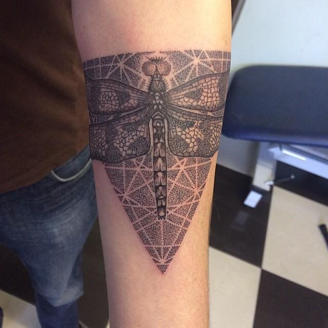 Designed dragonfly on triangle detailed dark colored tattoo on forearm in dotted work