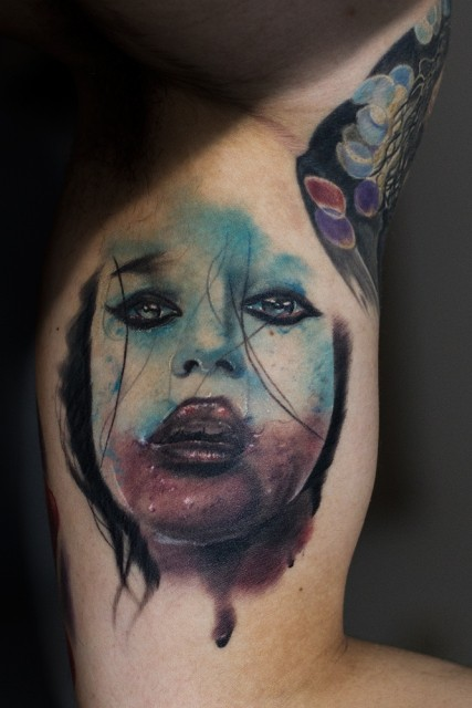 Detailed biceps tattoo of creepy woman face