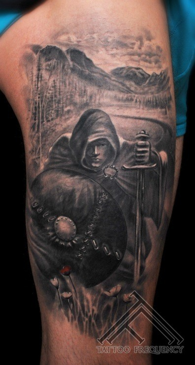 Detailed black and white cloaked man with sword and shield tattoo on shoulder
