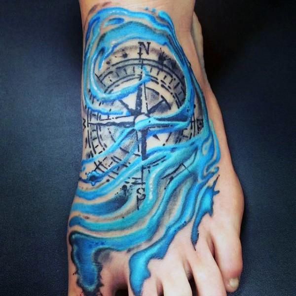 Tatuaje en el pie, compás en olas azules