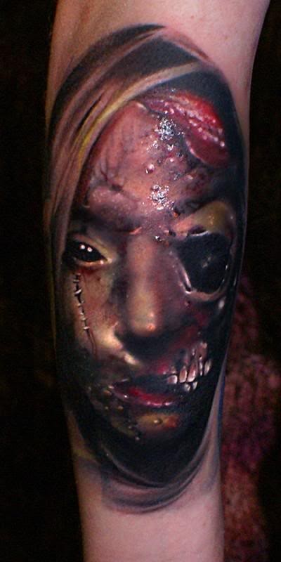 Detailed creepy looking leg tattoo of bloody monster face