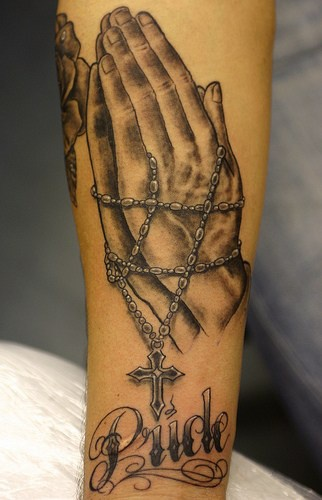 Detailed praying hands with rosary tattoo on arm