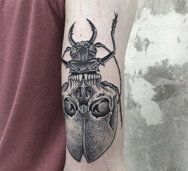 Dot style black ink arm tattoo of big bug combined with human skull