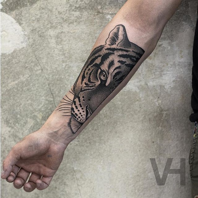 Dot style black ink forearm tattoo of split tiger head by Valentin Hirsch