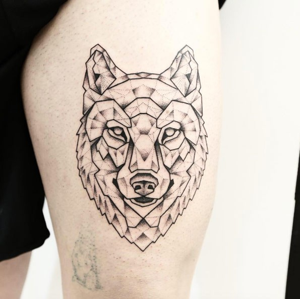 Dot style black ink thigh tattoo of wolf head