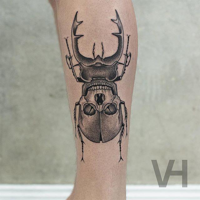 Tatuaggio del braccio dall&quotaspetto freddo alla moda di un grosso insetto stilizzato con un teschio umano