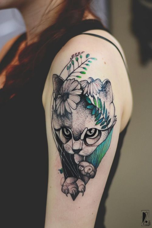 Dot style cute looking upper arm tattoo painted by Joanna Swirska of cat with flowers