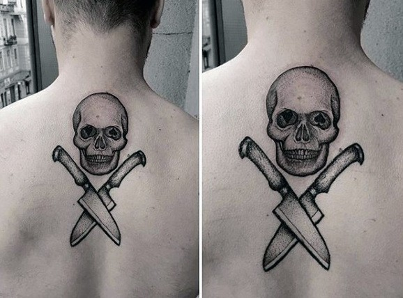 Dotwork style black ink upper back tattoo of human skull with crossed knifes