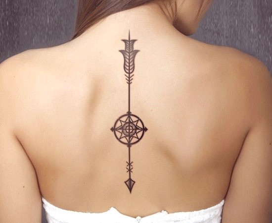 Downward arrow tattoo with compass on spine
