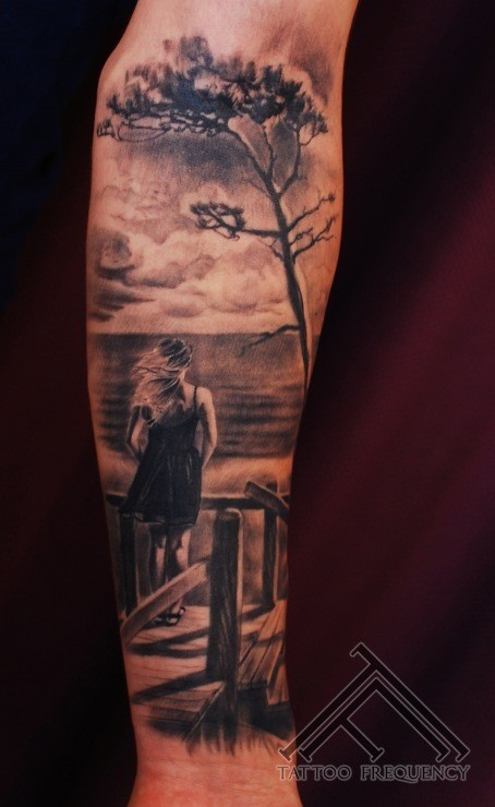 Dramatic black and gray style forearm tattoo of woman with tree and sea shore