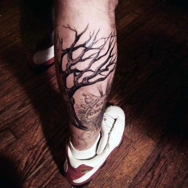 Dramatic black ink lonely tree on cemetery tattoo on leg