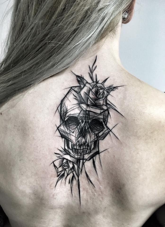 Dramatic black ink upper back tattoo of human skull with rose