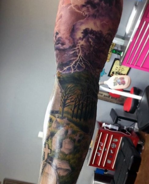 Dramatic colored sleeve tattoo of cemetery with dark sky and lightning