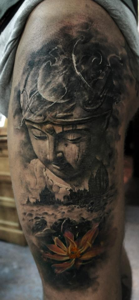 Dramatic dark colored shoulder tattoo of Buddha statue with colored lotus flower