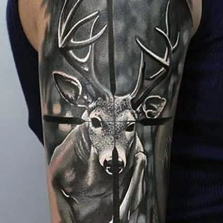 Dramatic hunting themed black ink deer in rifle scope tattoo on arm