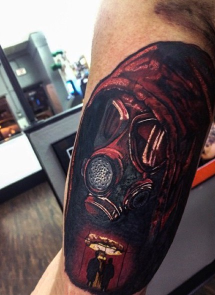 Dramatic illustrative style colored mad in gas mask tattoo on arm stylized with nuclear blast