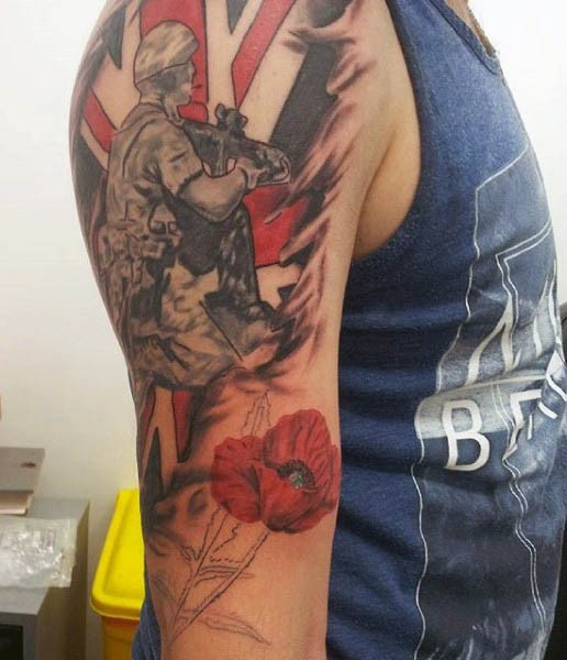 Dramatic military themed memorial tattoo on shoulder with soldier and flowers
