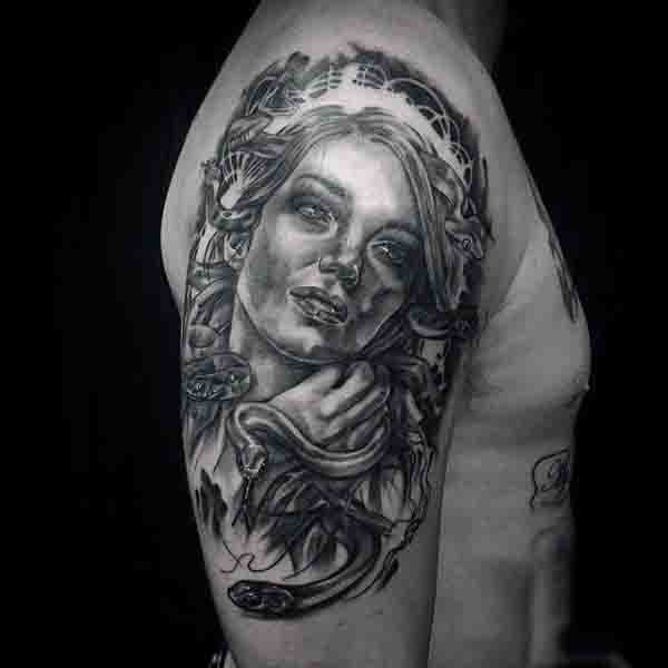 Dramatic painted black and white Medusa portrait tattoo on shoulder