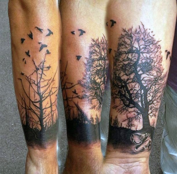 Dramatic painted black ink old dark forest with birds tattoo on wrist