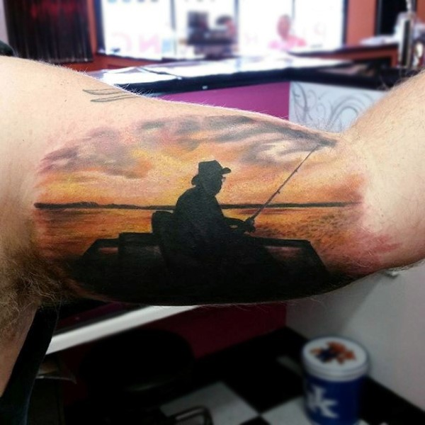 Dramatic painted colorful tattoo with old fisherman and sunrise on biceps