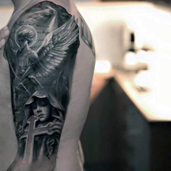 Dramatic religious black ink angel tattoo on shoulder with lettering and woman with big cross