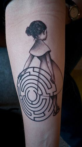 Dramatic style black and white little girl with hypnotic symbol tattoo on arm