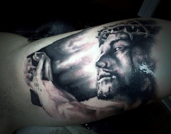 Dramatic style black ink biceps tattoo of Jesus portrait