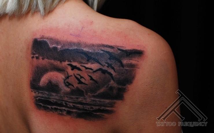 drammatico stile colorato riva del oceano  oceano con il sole e uccello tatuaggio su spalla