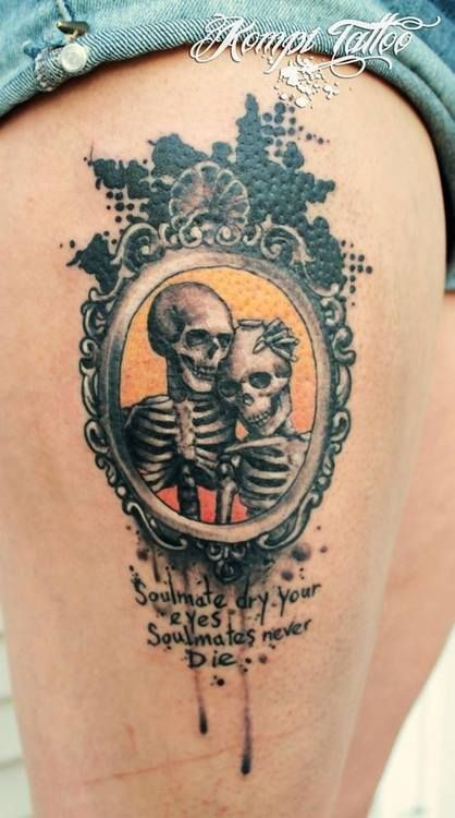 Dramatic style painted old skeleton couple portrait with lettering tattoo on thigh