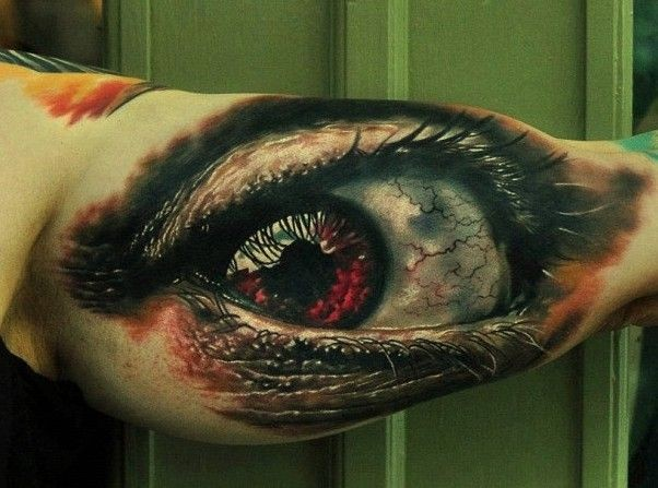 Dreadful red eye tattoo on arm