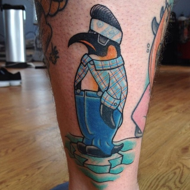 Dressed penguin tattoo standing on ice