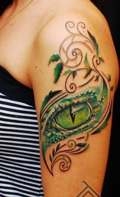 elegante occhio verde rettile con modello tatuaggio su spalla