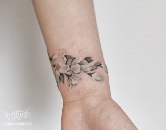 Elegant white and gray cherry blossom tattoo on wrist by Graffitoo
