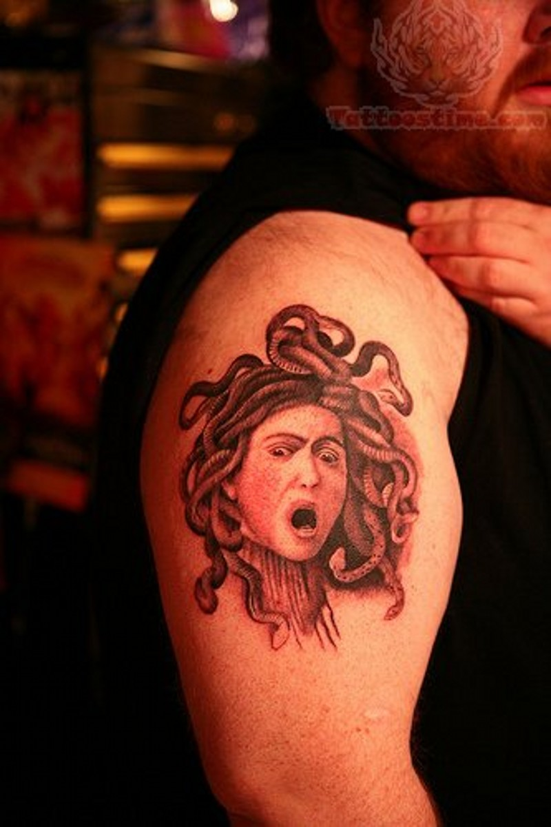 Engraving like black ink shoulder tattoo of small Medusa head