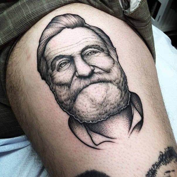 Engraving style beautiful looking thigh tattoo of smiling old man face